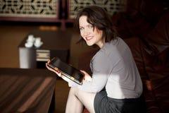 Menina bonita com uma tabuleta no café Fotografia de Stock