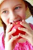 A menina bonita come a laranja Fotografia de Stock