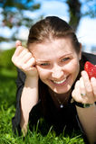 A menina bonita come a morango vermelha do frash no verde Fotos de Stock Royalty Free