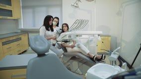A menina bonita consulta com o dentista na cadeira dental usa a imagem do raio X 4K video estoque