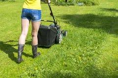 A menina bonita corta o cortador de grama de gramados de sega do gramado no fim de sega da ferramenta do trabalho do cuidado do j Foto de Stock Royalty Free