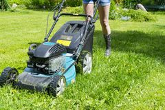 A menina bonita corta o cortador de grama de gramados de sega do gramado no fim de sega da ferramenta do trabalho do cuidado do j Imagem de Stock Royalty Free