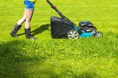 A menina bonita corta o gramado, gramados de sega, cortador de grama na grama verde, equipamento da grama da segadeira, ferrament Imagens de Stock Royalty Free