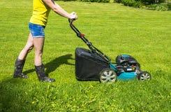 A menina bonita corta o gramado, gramados de sega, cortador de grama na grama verde, equipamento da grama da segadeira, segando a Fotografia de Stock