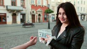 A menina bonita dá a um subôrno um grupo dos dólares Uma mulher faz as mãos de fricção de um crime antes de fazer o dinheiro pror video estoque