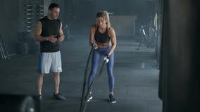 A menina bonita da aptid?o com instrutor est? fazendo o treinamento usando a corda do crossfit Exerc?cio no gym movimento 4k lent video estoque