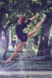 Menina bonita da bailarina na roupa ocasional que levanta em um fundo borrado das árvores do parque no close up dos pés do fundo imagens de stock royalty free