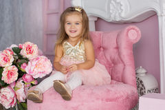 A menina bonita da criança está sentando-se na cadeira cor-de-rosa fotos de stock royalty free