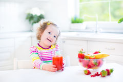 Menina bonita da criança que come o suco bebendo do café da manhã Fotos de Stock