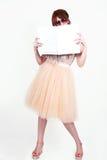 Menina bonita da forma que guarda um cartaz vazio para o texto ou o anúncio Imagem de Stock Royalty Free