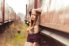 A menina bonita da hippie com cabelo vermelho e os bordos grandes está perto do carro velho perto da estrada de ferro Fotografia de Stock