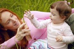 Menina bonita da matriz e do bebê ao ar livre fotografia de stock