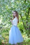 Menina bonita da mola na árvore de florescência imagem de stock