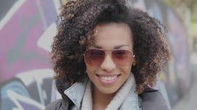 Menina bonita da raça misturada com o cabelo encaracolado que levanta no cenário urbano da cidade filme