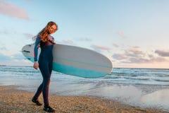 A menina bonita da ressaca com o cabelo longo que guarda a prancha vai na praia no por do sol ou no nascer do sol Imagem de Stock Royalty Free