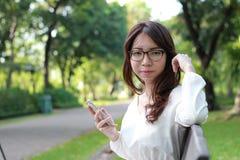 Menina bonita da universidade tailandesa do estudante de mulher que usa seu telefone esperto Fotos de Stock Royalty Free
