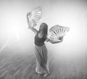 A menina bonita dança elegantemente no fumo e na névoa Fotografia de Stock