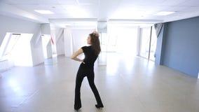 A menina bonita dança expressively nos saltos altos no salão de baile video estoque