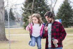 A menina bonita das pessoas de 5 anos que balança em um campo de jogos empurrou pelo paizinho Fotografia de Stock