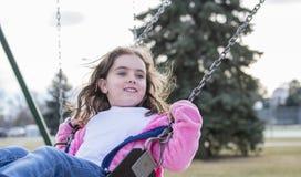 Menina bonita das pessoas de 5 anos que balança fora em um campo de jogos Fotos de Stock