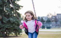 Menina bonita das pessoas de 5 anos que balança fora em um campo de jogos Fotografia de Stock Royalty Free