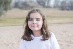 Menina bonita das pessoas de 5 anos que joga fora em um campo de jogos Foto de Stock
