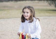 Menina bonita das pessoas de 5 anos que joga fora em um campo de jogos Imagens de Stock Royalty Free