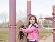Menina bonita das pessoas de 5 anos que joga fora em um campo de jogos Fotografia de Stock