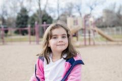 Menina bonita das pessoas de 5 anos que joga fora em um campo de jogos Imagem de Stock