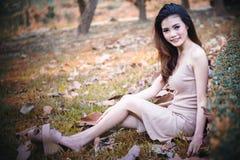Menina bonita de Ásia que senta-se no parque na grama verde fotografia de stock