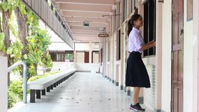A menina bonita de High School do estudante tailandês relaxa e jogando na escola video estoque