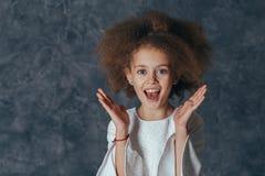 A menina bonita de sorriso com cabelo encaracolado guarda as mãos perto da cara e é deleitada imagem de stock