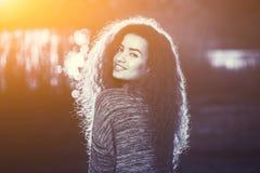 Menina bonita de sorriso com encaracolado, cabelo iluminado pelo sol em um fundo bonito do fundo de um por do sol do verão imagem de stock