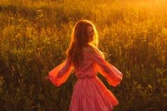 Menina bonita de sorriso de dança no vestido cor-de-rosa no campo, backl do sol Fotografia de Stock