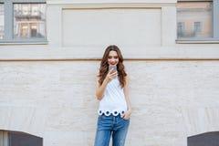 Menina bonita de sorriso dos jovens que usa seu telefone fora Foto de Stock