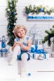 Menina bonita de sorriso pequena que senta-se ao lado de uma árvore de Natal fotos de stock