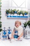 Menina bonita de sorriso pequena que senta-se ao lado de uma árvore de Natal e foto de stock royalty free