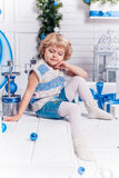 Menina bonita de sorriso pequena que senta-se ao lado de uma árvore de Natal e fotos de stock royalty free