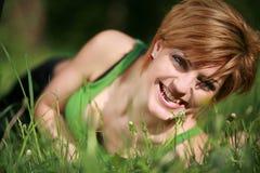 Menina bonita de sorriso que encontra-se na grama fotografia de stock