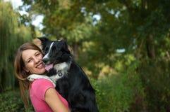 Menina bonita de sorriso que guarda seu cão branco e preto nas mãos durante o dia de verão Fotografia de Stock Royalty Free