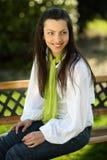 Menina bonita de sorriso que senta-se em um banco Fotos de Stock