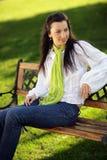 Menina bonita de sorriso que senta-se em um banco fotografia de stock royalty free