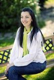 Menina bonita de sorriso que senta-se no banco Fotos de Stock