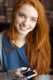 Menina bonita de Ssmiling com cabelo vermelho longo usando o smartphone Imagem de Stock