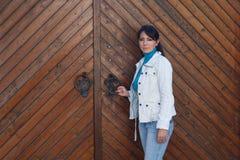 Menina bonita dentro no revestimento branco perto da porta de madeira Imagens de Stock Royalty Free
