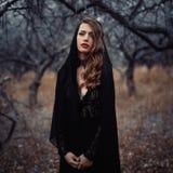 Menina bonita dentro no vestido preto do vintage com o cabelo encaracolado que levanta nas madeiras A mulher no vestido retro per Fotografia de Stock Royalty Free