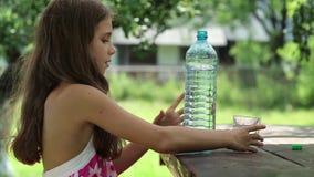 A menina bonita derrama a água da garrafa em um vidro filme