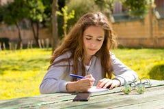 Menina bonita do adolescente com o smartphone m?vel do cellpfone no parque do ver?o foto de stock