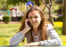 Menina bonita do adolescente com o smartphone m?vel do cellpfone no parque do ver?o imagem de stock
