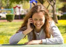 Menina bonita do adolescente com o smartphone m?vel do cellpfone no parque do ver?o imagens de stock royalty free